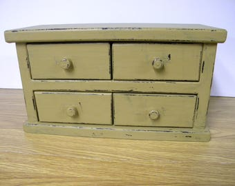 Four drawer apothecary table or counter cabinet. Distressed mustard with lamp black paint