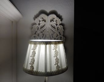 electric wall sconce made of lace wood and its pleated Lampshade decorated with pink trim
