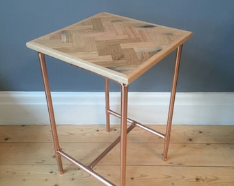 Side table in a retro industrial style with a copper pipe frame and reclaimed hard wood herringbone/parquet style top