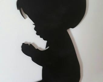 silhouette of a child in prayer, boy or girl.