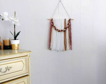 Pink, brown, and white yarn wall hanging