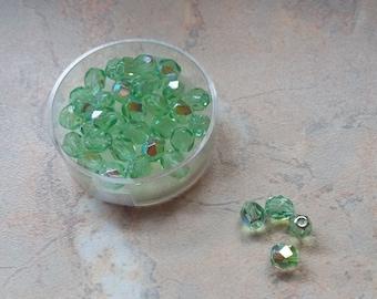 Faceted 6 mm light green iridescent glass beads