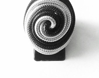 Ribbed aluminum spiral ring. Black and silver tone.