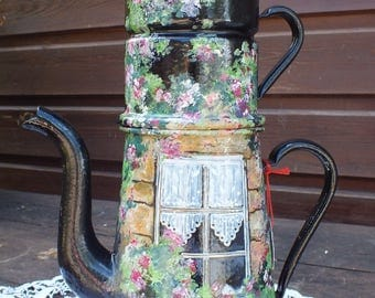 Very large retro coffee pot painted black with a white window on a small garden flowers