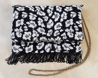 Clutch bag with flap with fringes.
