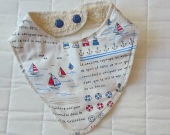 Bandana bib made of a cotton fabric, white background with marine motifs (sailboat, anchor
