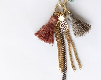 Crochet necklace with embroidered glass beads, tassels, a charm with pineapple form and necklaces of different shapes and shades of gold