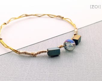 Stackable Brass Bangle wire-wrapped with geometric matte lustre hematite beads and a single iridescent crackle glass bead