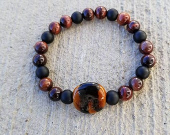 Brown Kazuri bead with black stripes, accented with matte black Onyx and red tiger's eye beads