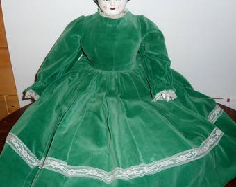vintage china doll dressed in green velvet dress