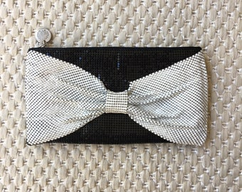 Black clutch with white bow detailing on front.