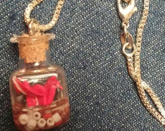Tiny red origami crane in a glass bottle necklace