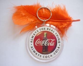 "Large round cabochon plastic ""Drink well known"" keychain."