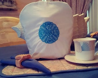 Teal motif embroidered on white  tea cozie for tea pot