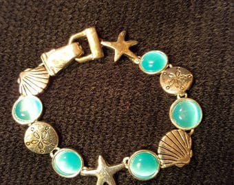 Nautical shell charm bracelet aqua blue cats eye beads. Silver tone magnetic clasp