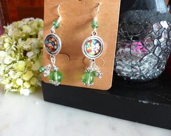 A pair of earrings with green cabochon