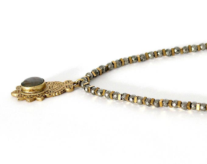 Necklace with an ethnic pendant and pyrite beads