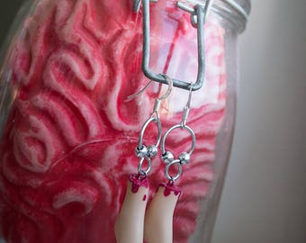 Dismembered barbie leg earrings with metallic detail