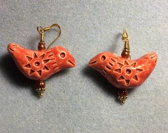 Large dark orange ceramic bird bead earrings adorned with orange Czech glass beads.