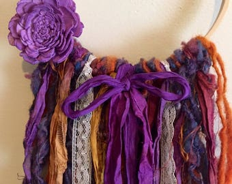 Art yarn wall hanging, art yarn, sari silk ribbons, lace, sola wood flower, purple and orange