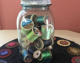 Vintage Blue Ball Jar filled with Wooden Spools of Thread