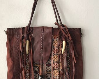 Brown leather hand bag with carpet .