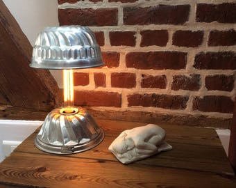 Lamp made with two upcycled molds cake together by the bulb