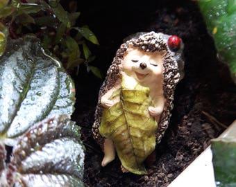 Sleeping hedgehog with leaf blanket figurine