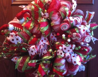 Deco mesh and ribbon christmas wreath. Embellished with elves feet, peppermint sticks and cute red and green berries.