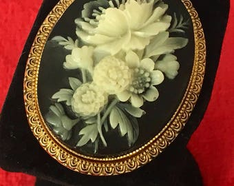 Vintage cameo gold tone brooch featuring cream flowers on black background
