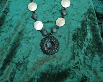 Black and silver disks with metal filigree pendant.
