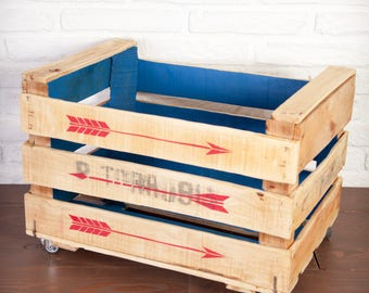 Fruit box restored and painted in blue with red arrows inside.