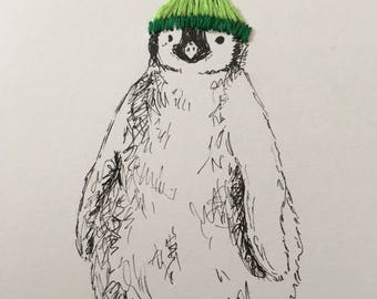 Framed, pen and ink penguin with embroidered bobble hat