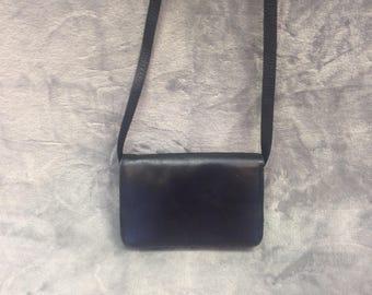Small black soft leather saddle bag with adjustable shoulder strap.