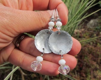 Dangle earrings with white and translucent faceted glass beads and antiqued, brushed silver plated zinc, hammered discs