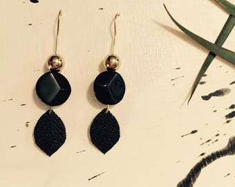 Black/gold earrings with a leaf