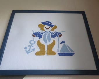 cross stitch Embroidery with a bear and his hat, anchor and boat