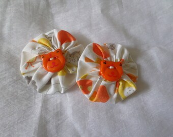 set of two clips made with white fabric yoyo with orange & grey flowers