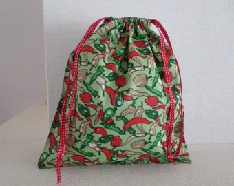 Pouch with green, red peppers, beige on a light green background