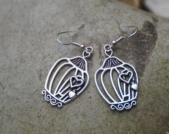 Silver cage containing a heart shaped earrings