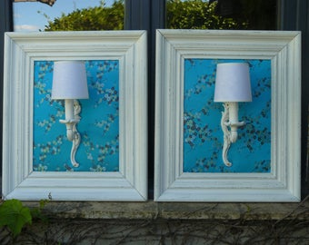 White wall sconces in white frames on turquoise background