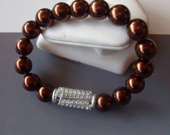 Brown pearl bracelet and white rhinestones.