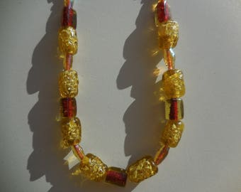 woman in yellow and bronze glass beads necklace