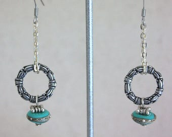 Earrings mounted in turquoise glass beads.