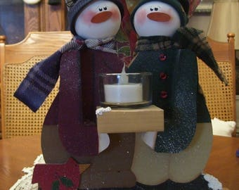 Snowbuddies holding candle