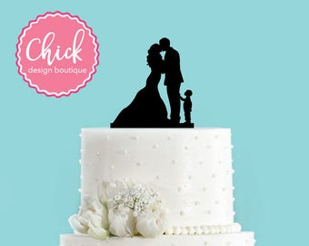 Couple Kissing with Little Boy Pointing at Bride and Groom Wedding Cake Topper