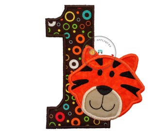 Tiger number one birthday iron on in bright orange with black stripes on top of modern, circle print fabric with brown background