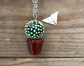 green round succulent full of thorns and with a tiny flower handblown glass pendant