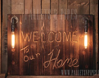 Routed pallet wood sign with industrial lighting. Rustic wood sign on burnt/torched pallet wood, hand routed with phrase of your choice.