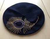 A Navy beret embellished with peacock feather